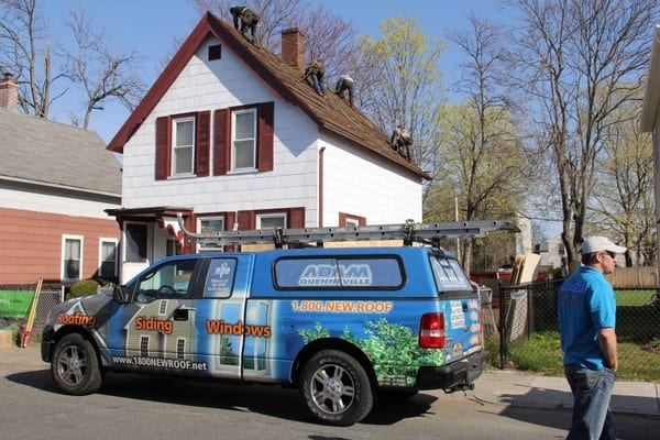 This is a photo of a local roofing replacement project with an Adam Quenneville truck in front of the house.