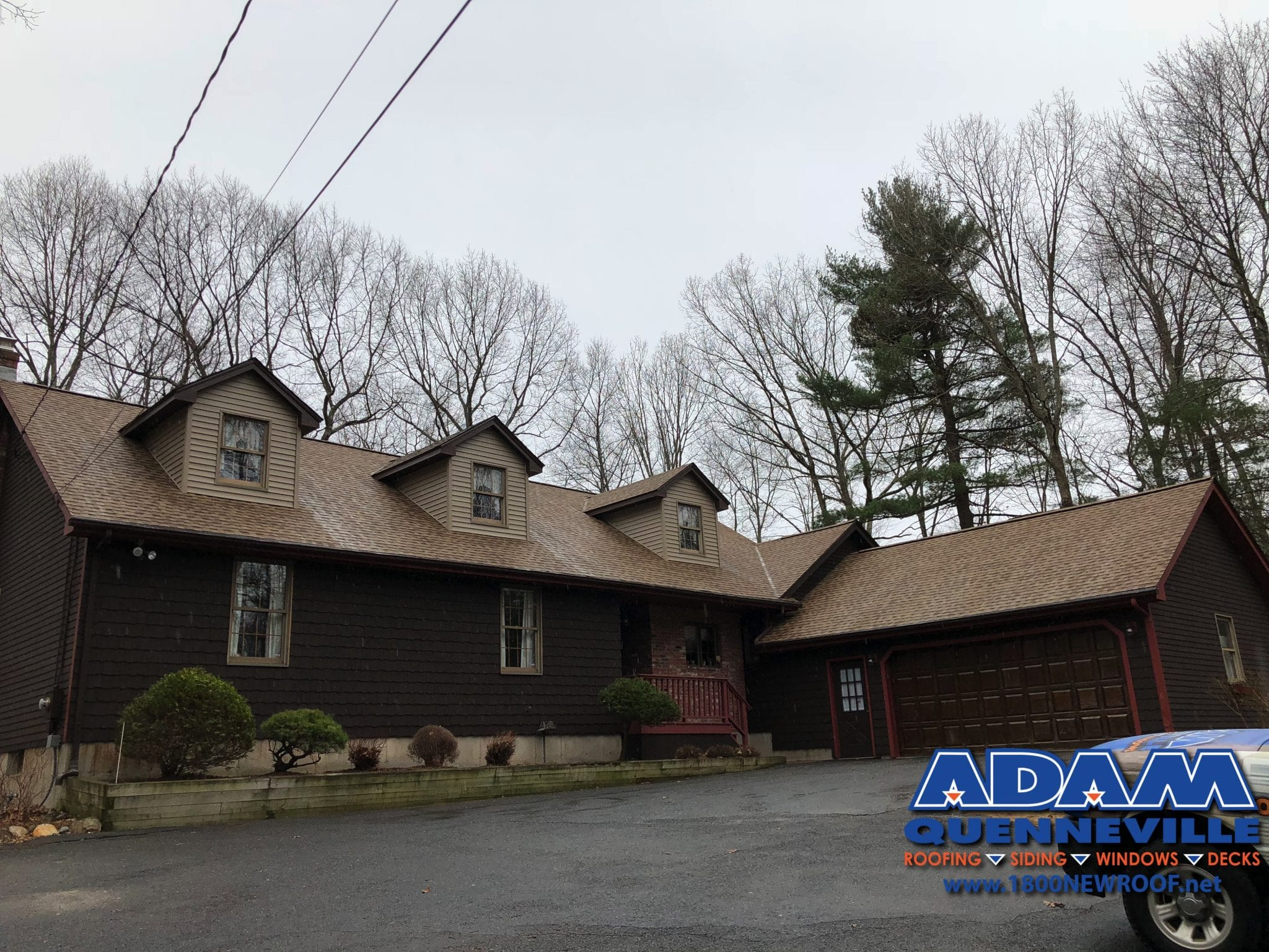 This is a photo of a completed roofing and riding replacement project with brown shingles.