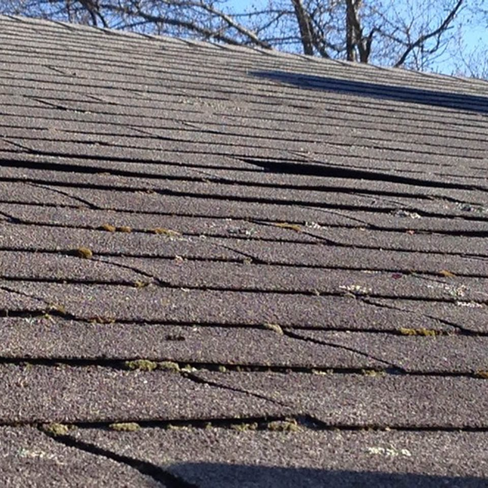 This is a photo of a roof in need of repair. Shingles are dry and cracking.