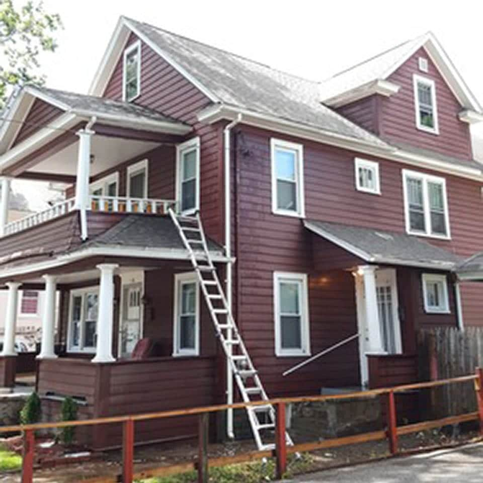 This is an after photo of a roof replacement project on a red house in Springfield, MA